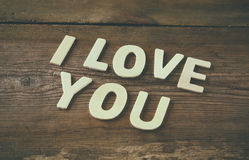 Selective focus photo of The words i love you made with block wooden letters on wooden background. Royalty Free Stock Image