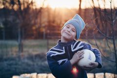 Selective Focus Photography of Boy Wearing Blue United Kingdom Print Zip-up Jacket Carrying White Ball Royalty Free Stock Photo