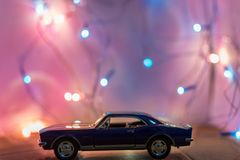 Selective Focus Photography of Classic Blue Coupe Die-cast Model in Front of String Lights on Table stock image