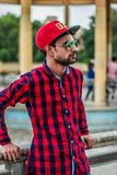 Selective Focus Photography of Man in Red and Black Gingham Sports Shirt Leaning on Grey Concrete Fence stock photo