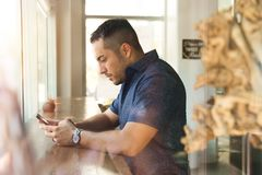 Selective Focus Photography of Man Sitting in Front of Brown Wooden Table While Holding Smartphone stock photo