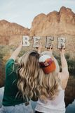 Selective Focus Photography of Two Women Holding Beer Cutout Letters royalty free stock image