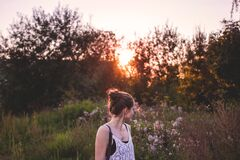 Selective Focus Photography of Woman Standing in the Middle of Grasses and Flowers during Golden Hour Stock Photo