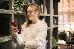 Selective Focus Photography of Woman Using Smartphone Beside Bookshelf Royalty Free Stock Images