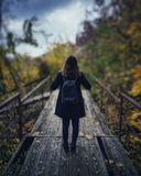 Selective Focus Photography of Woman Wearing Black Overcoat Standing on Wooden Bridge Stock Photography