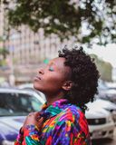 Selective Focus Photography of Woman Wearing Long-sleeved Shirt Closing Her Eyes Near Vehicles royalty free stock image