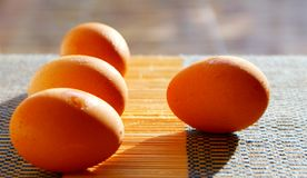 Selective focus picture of some fresh eggs. On bamboo weave pattern, close up soft focus background Stock Photos
