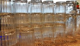 Selective focus. pile of empty transparent glasses on shelf. Close up of transparent clean glasses on a shelf, nested stock photography