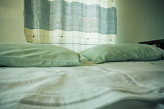 Selective focus on pillows and curtain of a small cozy bedroom Royalty Free Stock Images