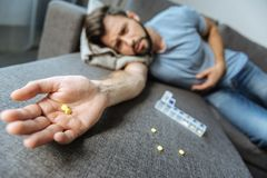Selective focus of pills lying on the male palm. Strong painkillers. Selective focus of pills lying on the palm of a sad depressed ill man while suffering from Stock Images