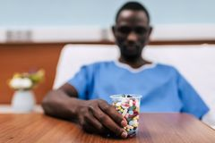 Pills in plastic glass. Selective focus of pills in plastic glass and african american man lying in hospital bed Royalty Free Stock Image