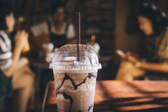 Selective focus of plastic iced chocolate cup with group of people having a conversation, playing guitar, reading a book and enjoy royalty free stock image