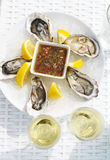 Selective focus point on fresh oysters shell with lemon and glas Royalty Free Stock Image