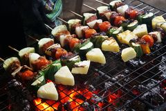 The selective focus pork Barbecue skewers on bamboo sticks with pineapple, tomatto, onion and chilli mushroom, bacon, sausage are stock images