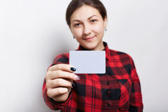 Selective focus. Portrait of female businesswoman in checked red shirt  holding a parchment business card with copy space for your Stock Image