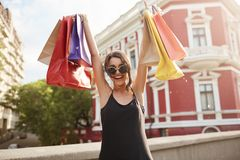 Selective focus. Positive emotions. Portrait of young beautiful dark-haired woman in sunglasses and black clothes. Holding colorful shopping bags under head Stock Photography