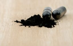Selective focus on powders of activated charcoal on brown wooden table Royalty Free Stock Photo
