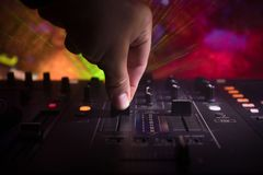 In selective focus of Pro dj controller.The DJ console deejay mixing desk at music party in nightclub with colored disco lights. royalty free stock photo