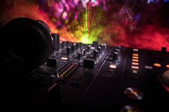 In selective focus of Pro dj controller.The DJ console deejay mixing desk at music party in nightclub with colored disco lights. Close up view stock photo
