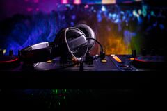 In selective focus of Pro dj controller.The DJ console deejay mixing desk at music party in nightclub with colored disco lights. Close up view royalty free stock image