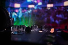 In selective focus of Pro dj controller.The DJ console deejay mixing desk at music party in nightclub with colored disco lights. Close up view royalty free stock photos