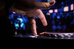 In selective focus of Pro dj controller.The DJ console deejay mixing desk at music party in nightclub with colored disco lights. royalty free stock photography