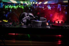 In selective focus of Pro dj controller.The DJ console deejay mixing desk at music party in nightclub with colored disco lights. Close up view stock images