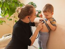 Selective focus Professional pediatrician examining to a little boy. Doctor using a stethoscope to listen to infant`s chest check. Ing heartbeat or lung Royalty Free Stock Images