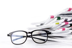 Selective focus on reading eyeglasses with stacking of newspaper Royalty Free Stock Images