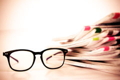 Selective focus on reading eyeglasses with stacking of newspaper Royalty Free Stock Photography