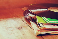 Selective focus of records stack with record on top over wooden table. vintage filtered.  stock photography