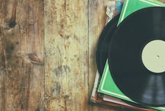 Selective focus of records stack with record on top over wooden table. vintage filtered.  stock image