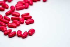 Selective focus of red kidney shape sugar coated tablet pills on. White background with copy space Royalty Free Stock Photography