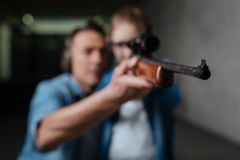 Selective focus of a rifle muzzle. I am ready. Selective focus of a rifle being help by a clever young curious girl while standing with her father Stock Image