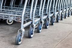 Selective focus on row of shopping carts at supermarket entrance royalty free stock images