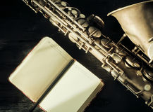 Selective focus on saxophone and open notebook Stock Photo