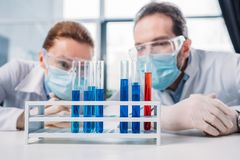Selective focus of scientific researchers in googles and medical masks looking at reagents in tubes. In lab stock photo