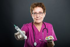 Selective focus of senior lady doctor holding syringe and pills. On black background Stock Images