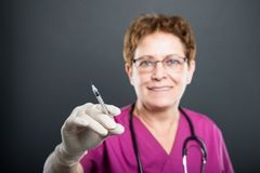 Selective focus of senior lady doctor holding syringe. And smiling on black background with copyspace advertising area Royalty Free Stock Photos