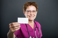 Selective focus of senior lady doctor showing business card. And smiling on black background Stock Image
