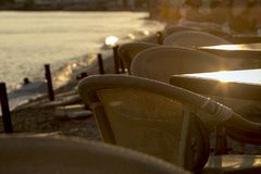 Selective focus on a series of tables and wooden chairs by the coast at sunset. royalty free stock images