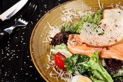 Selective focus on served Caesar salad with Salmon on dark background. royalty free stock photography