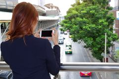 Selective focus and shallow depth of field. Back view of woman taking a photo of traffic car in city with mobile smart phone.  stock images