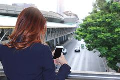 Selective focus and shallow depth of field. Back view of woman taking a photo of traffic car in city with mobile smart phone.  Stock Photography