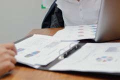Selective focus and shallow depth of field on charts or paper work on the desk between meeting in conference room.  Stock Photo