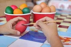 Selective focus and shallow depth of field. Easter eggs are painted with paintbrush by little boy. Selective focus and shallow depth of field. Easter eggs are Stock Images