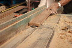 Selective focus and shallow depth of field. A piece of wood is being shaved on a router table by hands of carpenter in carpentry w Stock Photography