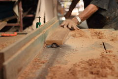 Selective focus and shallow depth of field. A piece of wood is being shaved on a router table by hands of carpenter in carpentry w Royalty Free Stock Photography