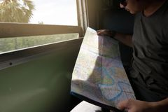 Selective focus and shallow depth of field. Young Asian hipster exploring location on the map in the train. Shallow depth of field.  Royalty Free Stock Photography