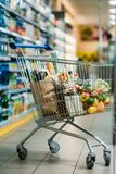 Selective focus of shopping cart with purchases. In supermarket royalty free stock images